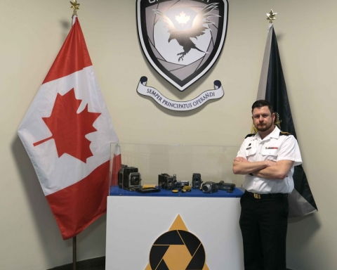 Chief Petty Officer 1st Class (CPO 1) Shawn M. Kent, Public Affairs Branch Chief Warrant Officer, poses in the foyer of the Operational and Technical Imagery Centre (OPTIC) in Ottawa, Ontario. Displayed in the foyer is a small collection of cameras used by military photographers over the past 100 years as well as the unit crest and Imagery Technician occupation badge of an aperture over a prism (the primary tools of the photographer/videographer to bend and control light).
